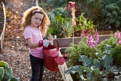 Little girl with watering can at community garden